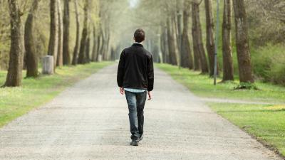 Boy walking on the road in a park