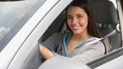 Portrait of teenage girl smiling in car