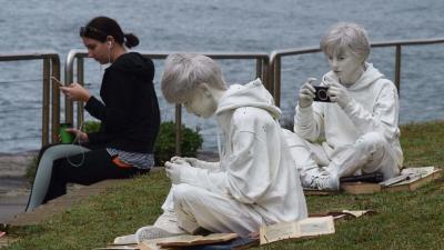 Egy nő mobiltelefonját használja Fabio Pietrantonio Quotidianity, the brothers (Hétköznapiság, a fivérek (2103)) című alkotása mellett az évente megrendezett tengerparti szoborkiállításon Sydney Bondi Beach és Bronte Beach közötti partszakaszán. (MTI/EPA/