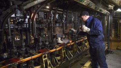 Egy dolgozó az üveggyártó gép formakenését végzi az O-I Magyarország Üvegipari Kft. orosházi gyárában 2017. január 25-én. MTI Fotó: Rosta Tibor