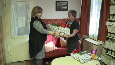 Bátori Zsuzsanna (j.) Varga Évának (b.) adja át a több mint száz darabból álló adományt jelképező csomagot. Fotó: Ujházi György