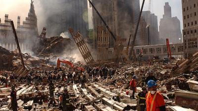 A Rendkívüli Helyzetek Szövetségi Hivatalának 2001. szeptember 13-i képe, amelyen tűzoltók és mentők túlélők után kutatnak a New York-i Világkereskedelmi Központ még mindig füstölő romjai között. A központ 110 emeletes ikertornyai szeptember 11-én dőltek