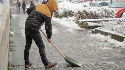 Egy férfi havat lapátol a Szabadság téren 2018.12.15.-én. Fotó: behir.hu/Varga Diána