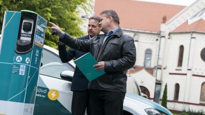 Siklósi Gábor az NKM Mobilitás Kft képviseletében magyarázza (b) Bojtor Istvánnak, Orosháza alpolgármesterének az e-töltő működését.