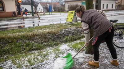 A jégeső után maradt jégdarabokat lapátolja a járdán egy nő Gádoroson, február 11-én (MTI/Rosta Tibor)