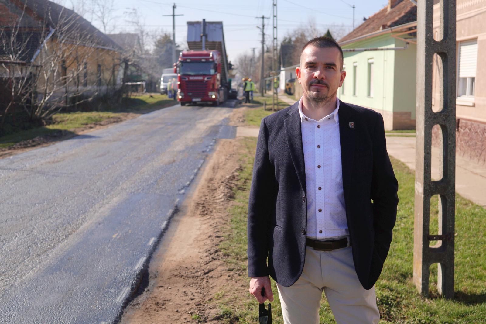 Ribárszki Péter, Kondoros polgármestere, háttérben az útépítés. Fotó: behir.hu/Vári Bianka
