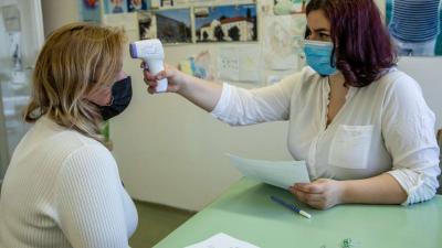 Berta Vivien asszisztens (j) egy férfi testhőmérsékletét méri, mielőtt beoltják a Szputnyik V koronavírus elleni vakcina első adagjával az orosházi Dr. László Elek Kórház és Rendelőintézet oltópontján 2021. április 13-án. MTI/Rosta Tibor