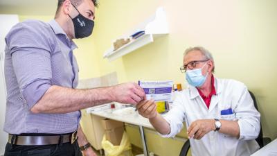 Kincses Zoltán orvos (j) átadja az oltási igazolást egy férfinek, miután beoltották a német-amerikai fejlesztésű Pfizer-BioNTech koronavírus elleni oltóanyag, a Comirnaty-vakcina első adagjával a Békés Megyei Központi Kórház, Dr. Réthy Pál Tagkórház egyik