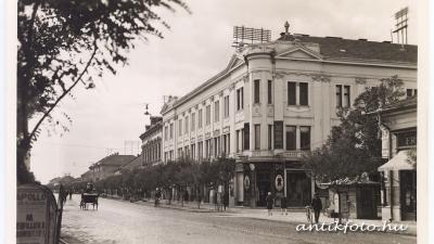 Az Andrássy út az 1930-as években; a jobb oldalon az egykori Frnda-féle ház sarka. Az Irányi utca szemközti oldalán a Kocziszky-palota, a fotó bal oldalán az Apolló Mozi hirdetése látható (antikfoto.hu, Tuska János gyűjteményéből)